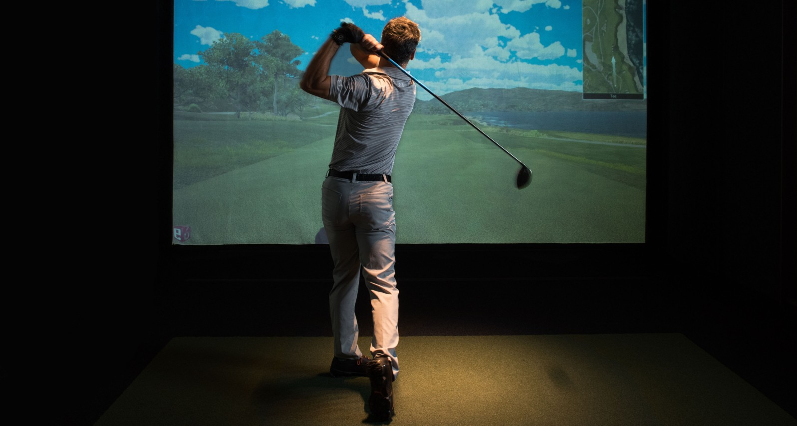 Ein Golf Spieler vor dem Golf Simulator beim Follow Through
